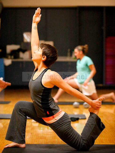 Ayumi Deeny, foreground, and pharmacy senior Ashley Stack do yoga exercises during the Yogamuscle class Wednesday night at the Johnson Center..Photo by Zach Brake | Staff
