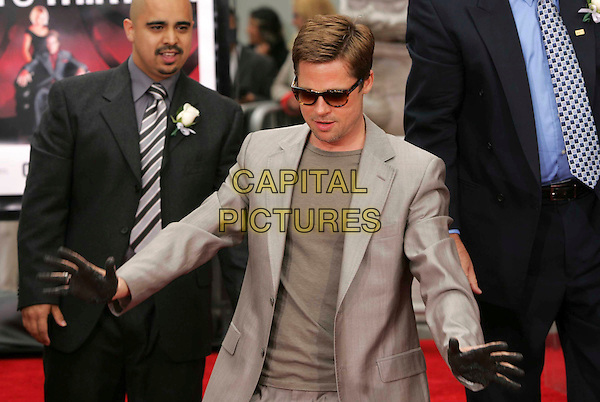 BRAD PITT.At The Warner Brothers' Hand & Foot Print Ceremony for Ocean's Thirteen at The Grauman's Chinese Theatre in Hollywood, California, USA..June 5th, 2006.half length beige suit jacket sunglasses shades hands palms dirty .CAP/DVS.©Debbie VanStory/Capital Pictures