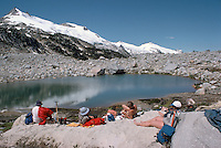 Hikers relaxing at Glacier Fed Tarn in Manatee Mountains, near Pemberton, BC, British Columbia, Canada, Summer
