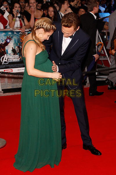 Elsa Pataky and Tom Hiddleston.'Marvel Avengers Assemble' European film premiere at Vue cinema, Westfield, London, England..19th April 2012.full length black suit white shirt green dress pregnant touching belly stomach side braid plait hair .CAP/AH.©Adam Houghton/Capital Pictures.