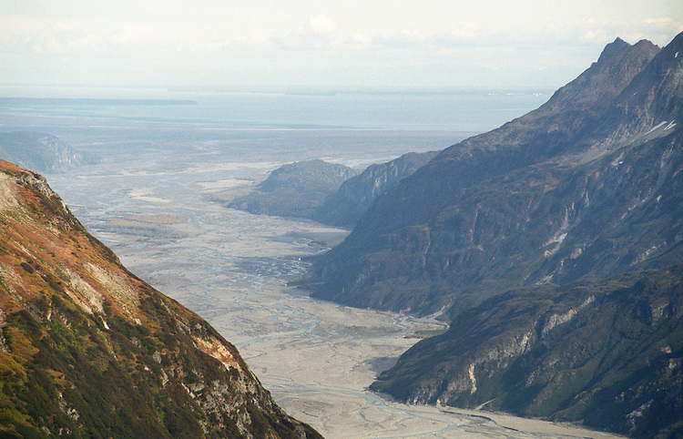 The Drift River valley drains toward Cook Inlet looking west, toward Kenai, Alaska, from Mount Redoubt's foothills. One threat posed by eruptions is flooding at the Drift River oil facility near the river's mouth on the shore of Cook Inlet....