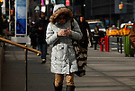 A woman plays by her phone as Low temperatures hit New York, United States. 23/01/2013 Photo by Kena Betancur/VIEWpress.