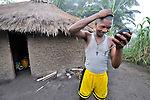 A man checks his appearance in a mirror outside his home in the Congolese village of Wembo Nyama