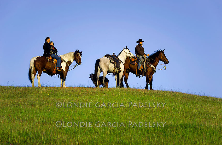 Family riding horseback on green hillside. San Luis Obispo, California