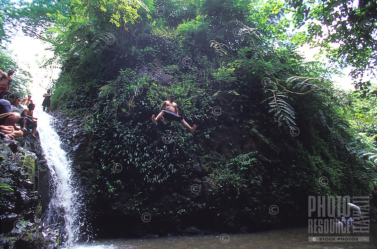 Local jumping into pool at jungle waterfall, Maunawili Trail, Kailua, Oahu. Hawaii