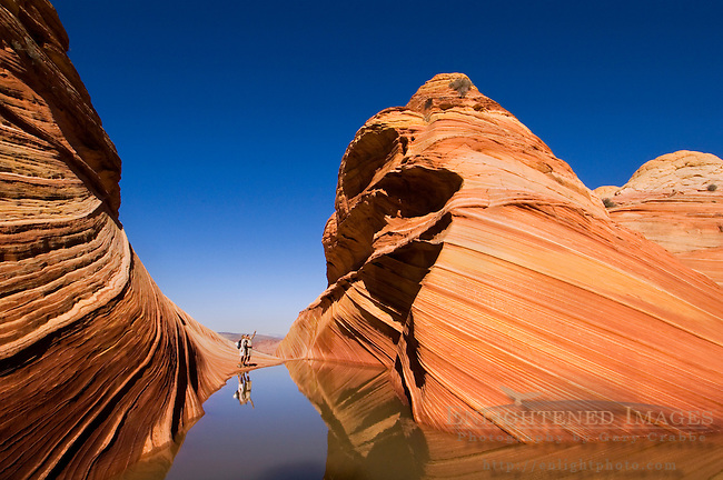 Tourist couple next to Seasonal desert pool of water below striated sandstone at The Wave, Coyote Buttes, Paria Canyon Vermilion Cliffs Wilderness, Arizona