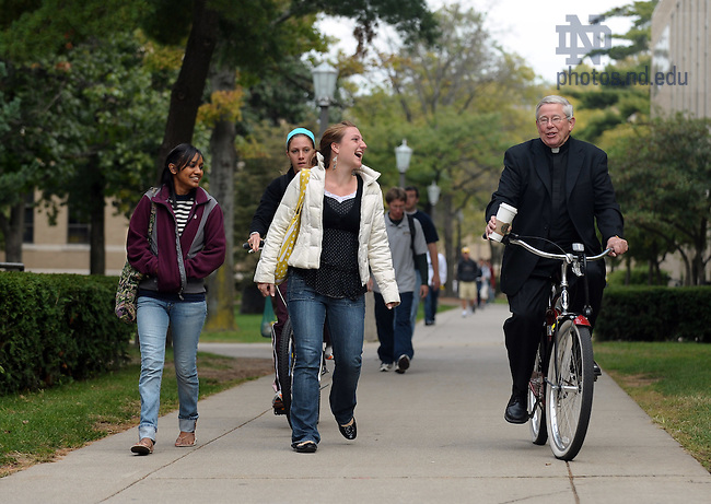 Fr. Joe Carey, C.S.C. rides his bike on campus...Photo by Matt Cashore