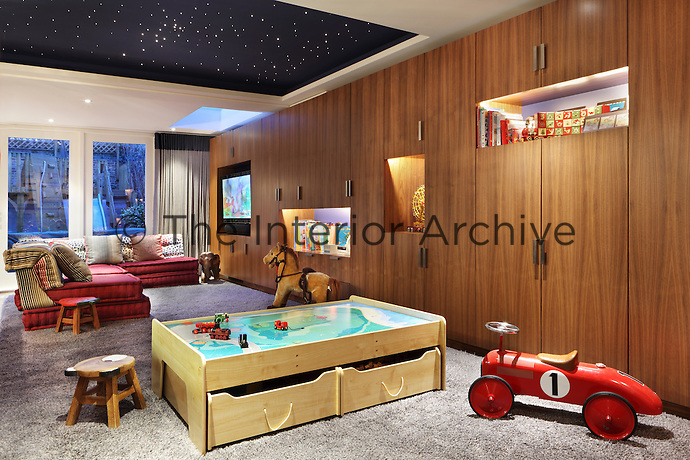 A child's playroom with a large fluffy rug and an array of entertaining toys
