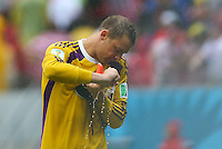 Germany goalkeeper Manuel Neuer wrings out his soaking wet goalkeeping gloves