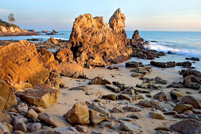 sunset on breaking waves and rocks at Corona Del Mar beach Newport Beach California