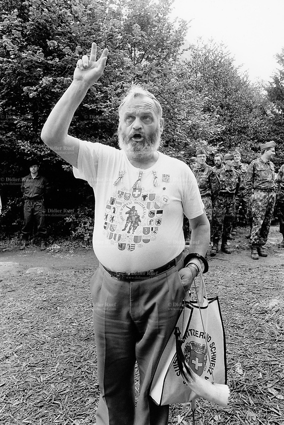 Switzerland. Canton Uri. Rütli feld. 1 August 1991. Swiss national holiday. Public holiday. A man with a beard takes an oath of allegiance to Switzerland by holding up his three fingers. He wears a t-shirt with: William Tell (Wilhelm Tell - Guillaume Tell), his crossbow and his son; the flags of the 26 swiss cantons; the words Suisse, Schweiz, Switzerland. Swiss flag. Soldiers in military outfitts and a policeman. Rütli is the birthplace of the Swiss Confederation. © 1991 Didier Ruef