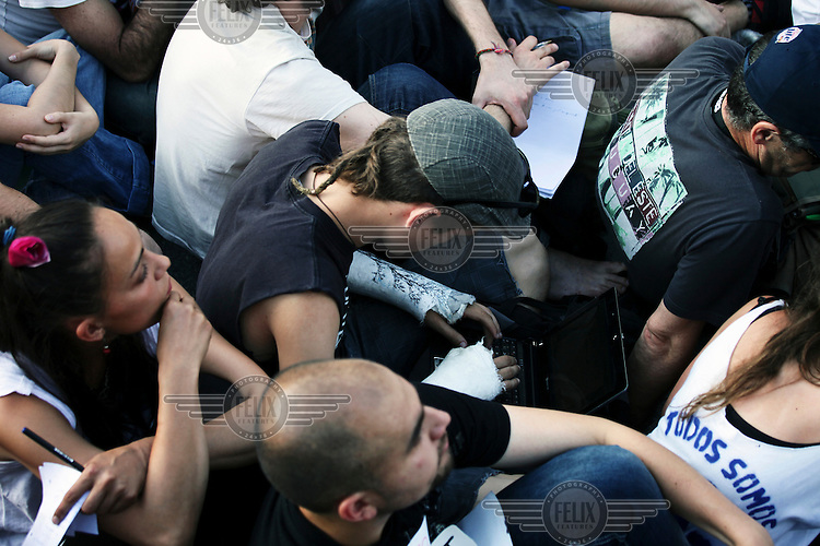 A young man with casts on both arms sits in a group of demonstrators during a protest against cuts, austerity and joblessness in Madrid's Puerta del Sol square. In May 2012, following a worsening financial crisis and a deepening recession in Spain, thousands of people started to gather in Spanish cities to protest against austerity, the global financial system, high unemplyment rate (Spain's is the highest rate in Europe) and the lack of opportunities. The protest movement has become known as 'los indignados' (the indignant ones).
