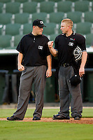 Home plate umpire Travis Godec (right) shows base umpire Cody Oakes how he makes an out call between innings of the South Atlantic League game between the West Virginia Power and the Kannapolis Intimidators at CMC-Northeast Stadium on July 9, 2013 in Kannapolis, North Carolina.  The Power defeated the Intimidators 3-1.   (Brian Westerholt/Four Seam Images)
