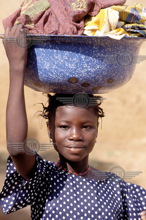 © Giacomo Pirozzi / Panos Pictures..MALI..Girl carrying clothes for washing at the village water pump.