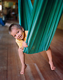 PERU, Amazon Rainforest, South America, Latin America, portrait of a cute child sitting on hammock at the Tambopata Research Center Lodge.