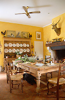 The bright Provencal-style kitchen has yellow walls and is furnished with a pine dresser and scrubbed table