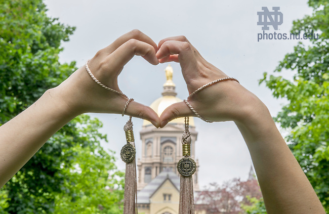 May 16, 2015; Graduates bring their hands together to form the shape of a heart in front of the Golden Dome. Photo by Barbara Johnston/University of Notre Dame