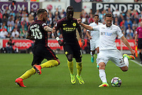 Gylfi Sigurdsson of Swansea City (R) crosses the ball past Nicolas Otamendi (L) and Bacary Sagna of Manchester City during the Premier League match between Swansea City and Manchester City at The Liberty Stadium in Swansea, Wales, UK. Saturday 24 September 2016