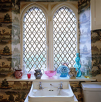 A collection of coloured glass is displayed against the mullioned window of the bathroom