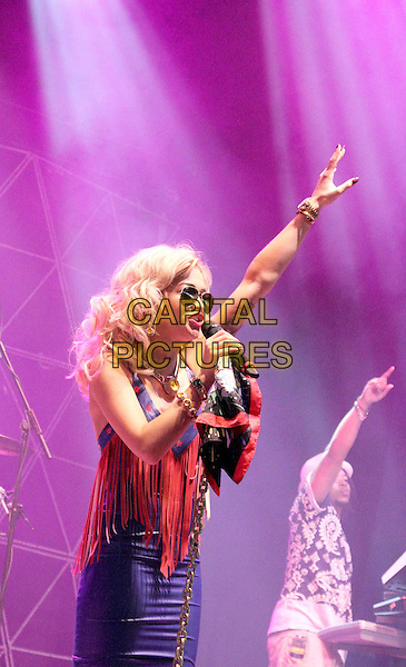 Rita Ora.V Festival 2012 - Day Two, Hylands Park, Chelmsford, Essex, England..August 19th 2012.on stage in concert live gig performance music half length orange red fringed profile side arm in air hand purple leather dress sunglasses shades singing.CAP/JIL.©Jill Mayhew/Capital Pictures