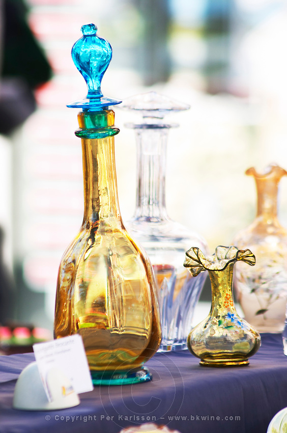 Street market merchant's stall with old coloured glass decanters and other glass ware Sanary Var Cote d'Azur France