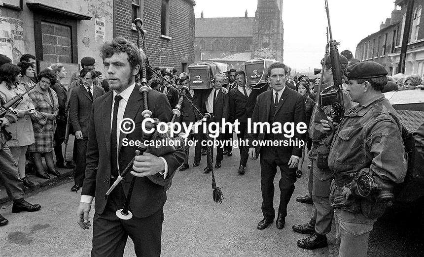 Piper heads the funeral cortege of Gerard O'Hare, 17 years, Roman Catholic, Belfast, and Rose Curry, 18 years, Roman Catholic, Lower Abercorn Street, Belfast, who died when a bomb exploded prematurely in a house in Merrion Street, Lower Falls, Belfast, on 23rd September 1971. They were members of the Official IRA. British soldiers look on impassively. 197109230354a.<br />