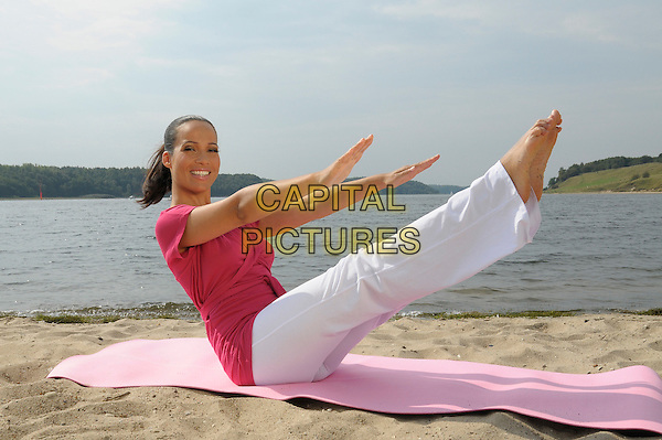 NANDINI MITRA.german moderator, privat story, surrounding area of Hamburg, Germany. .August 25th, 2009.full length pink top white trousers sitting pilates blanket legs up arms reaching exercise sand .CAP/RD.©Richard Dean/Capital Pictures.
