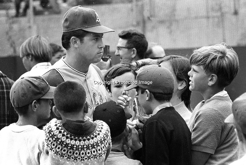 "Oakland A's pitcher Jim ""Catfish Hunter"" signs for a bunch of kids..(1969 photo/Ron Riesterer)"