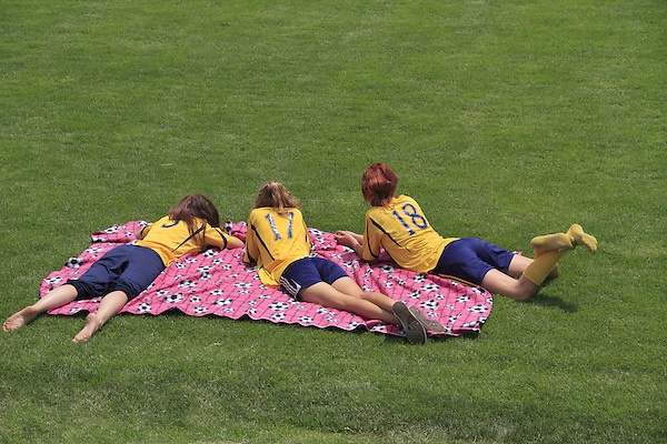 Girls resting on blanket after soccer game, Denver, Colorado, USA. .  John leads private photo tours in Boulder and throughout Colorado. Year-round.