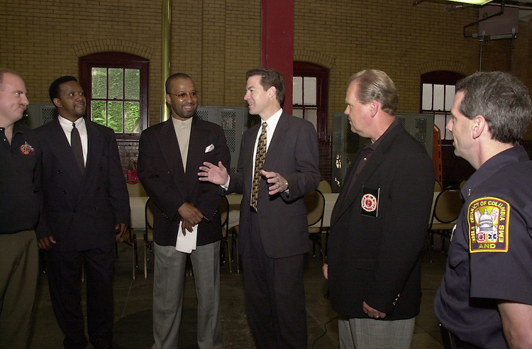 Brownback S.1(DG) 052300 -- Sam Brownback, R-Kan., jokes around with some of the firemen of Engine Company 3. Browback was there to receive an award for saving the lives of residents in his apartment building during a fire.