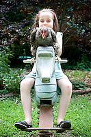 Cleo (daughter of Cynthia Deis) and Fi Fi take a ride together in Cynthia Deis' backyard in downtown Raleigh's Glenwood Brooklyn neighborhood.