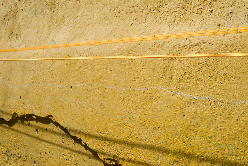 Yellow embroidery thread stretched to dry against the yellow walls in the medina, Fez.