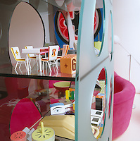 Glass shelves in the living room filled with objects designed by Karim Rashid
