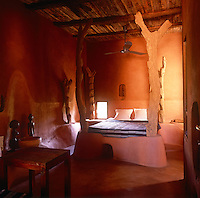 The interior of La Maison Rouge hotel with its distinctive red adobe contruction and Moroccan influence. a guest bedroom with posters made from tree trunks.