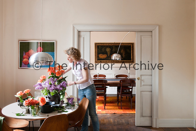 Interior designer Anna Johansson arranging flowers in the kitchen of her Milanese apartment with a view through the sliding doors into the dining room