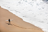 HAWAII, Oahu, North Shore, surfer exiting the water at Waimea Bay
