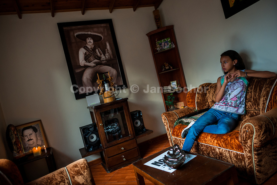 "A Colombian girl sits on a sofa in a living room, decorated by pictures of the drug lord Pablo Escobar, in a house in the Pablo Escobar neighborhood, Medellín, Colombia, 30 November 2017. Twenty five years after Pablo Escobar's death, the legacy of the Medellín Cartel leader is alive and flourishing. Although many Colombians who lived through the decades of drug wars, assassinations, kidnappings, reject Pablo Escobar's cult and his celebrity status, there is a significant number of Colombians who admire him, worshipping the questionable ""Robin Hood"" image he had. Moreover, in the recent years, the popular ""Narcos"" TV series has inspired thousands of tourists to visit Medellín, creating a booming business for many but causing a controversial rise of narco-tourism."