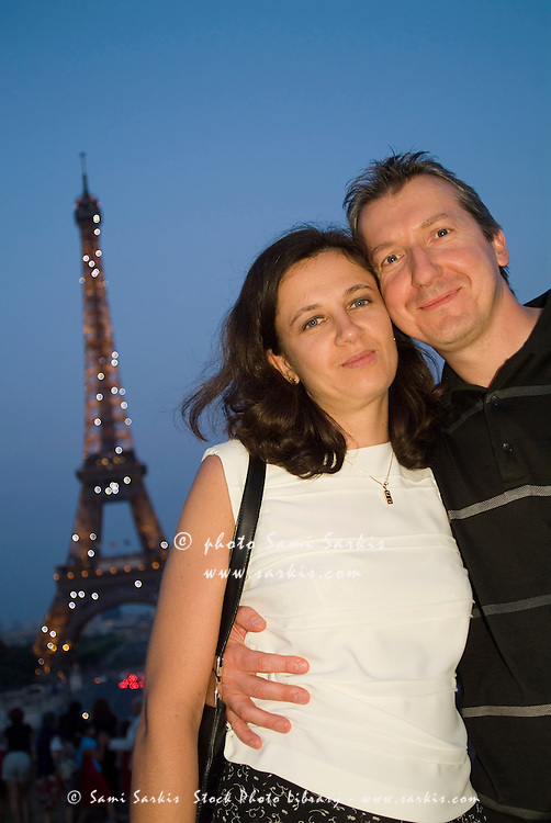 Couple smiling in front of Eiffel Tower at dusk, Paris, France.