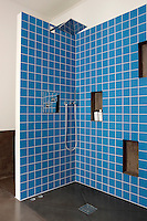 The shower area of the bathroom is lined with sky-blue tiles together with a series of practical niches