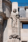 Detail of a building with large statues of women standing by the windows on the Avenida dos Aliados in Porto, Portugal.