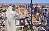Businessman stands at his office window while talking on his mobile phone, with his view of The Gate development, Dubai?s International Stock Exchange,the central business area under construction and tall buildings along Sheikh Zayed Road. Dubai. United Arab Emirates. Model released.