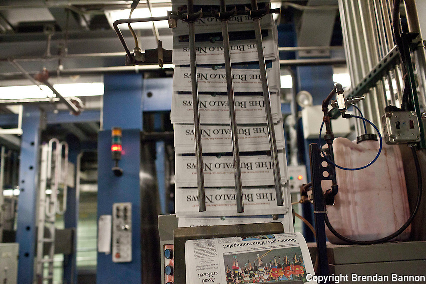 Copies of the Buffalo News run along a conveyor belt after they have been mechanically folded and assembled by the printing presses at The Buffalo News. The newspaper has been owned by billonaire investor Warren Buffett since 1977. Buffett announced the purchase of an additional 63 newspapers in May of 2012. Photo: Brendan Bannon, Buffalo, NY, June 8, 2012.