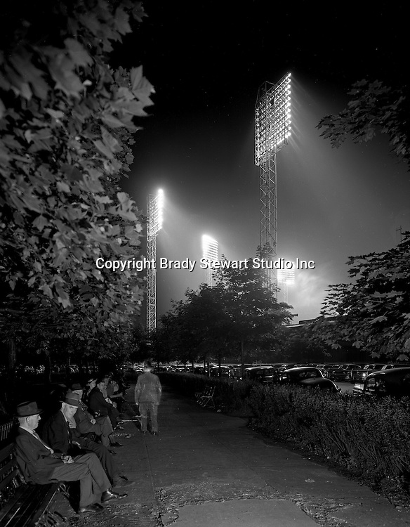 Pittsburgh PA:  During the depression, homeless men used to meet behind Forbes Field in Schenley Park during baseball games. They would listen to the game and talk with their friends - 1936.  This photograph took over a 30 second exposure to capture the lights and mist.  The man leaning forward on the bench got up and represents the ghost image walking down the walkway.