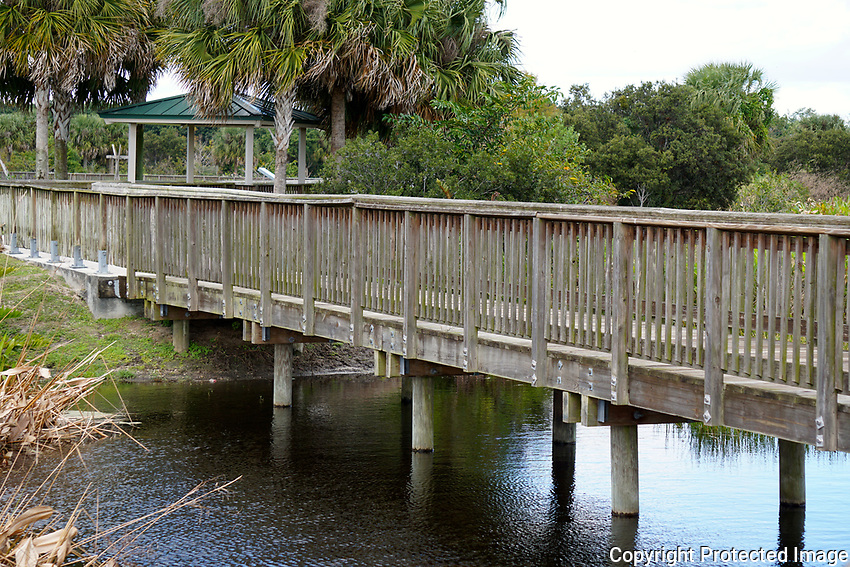 Walkway revealing warped railings and constant exposure to the Florida elements. Photographed at Wellington Peaceful Waters Sanctuary, Wellington, Florida.