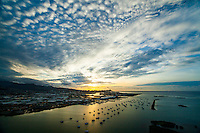 An aerial view of sunrise filtering through cloud formations and reflecting on the ocean at Ke'ehi Boat Harbor and Lagoon, Honolulu, O'ahu.