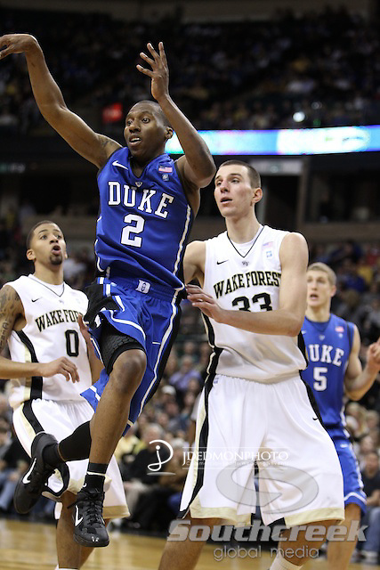 Duke Blue Devils guard Nolan Smith (2) goes up to dish off the ball as Wake Forest Demon Deacons center Carson Desrosiers (33) gurards. Duke wins 83-59..