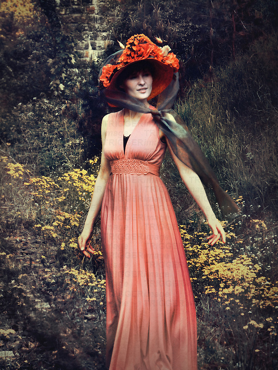 A woman in a pink flowing dress, and a bold red victorian hat with flowers, standing in front of a flowery background.