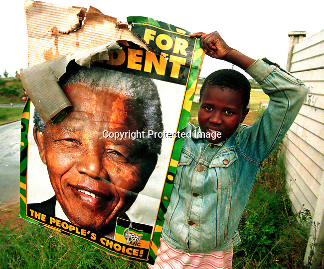 DIELECT00076.Polotics. Elections. A boy holding up an election poster in Lindelani, outside Durban, South Africa. President Nelson Mandela became the first democratic elected president in the election on February 29, 1994 in South Africa..©Per-Anders Pettersson@iAfrika Photos