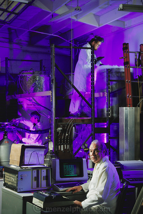 Cryonics: Art Quaif (seated at computer) and a colleague at Trans Time Inc., a cryonics company in Oakland, California. In the stainless steel vats full of liquid nitrogen are dead human bodies. Cryonics is a speculative life support technology that seeks to preserve human life in a state that will be viable and treatable by future medicine. Cryonics involves the freezing of whole human bodies, organs or pet cats & dogs, and their preservation in liquid nitrogen to await a future thaw. Cryonicists claim that medical science in the future may offer a cure for cancer or the restoration of youth, and that their methods of preservation might offer some people an opportunity to benefit from these advances. Conventional cryobiology methods for freezing organs (for organ transplants, for example) are plagued by problems of intracellular ice crystal formation, which destroys their component cells. MODEL RELEASED 1987..