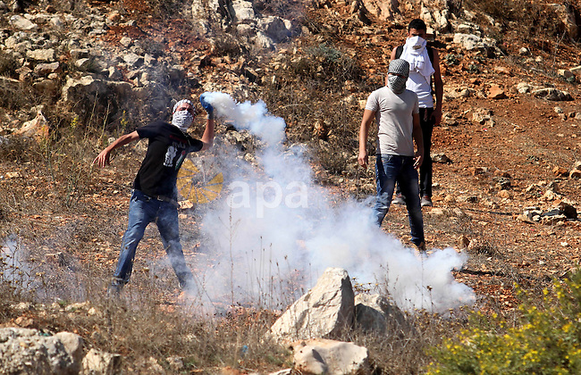 A Palestinian protester throws back a tear gas canister fired by Israeli security forces during clashes at a protest to show solidarity with al-Aqsa mosque, outside Israel's Ofer military prison near the West Bank city of Ramallah October 21, 2014. A Palestinian official on Monday called for holding an emergency Arab and Islamic summit to discuss Israeli plans to divide the Al-Aqsa Mosque compound between Jews and Muslims. In recent months, groups of Jewish settlers accompanied by Israeli security forces have repeatedly forced their way into East Jerusalem's flashpoint Al-Aqsa Mosque complex. Photo by Shadi Hatem